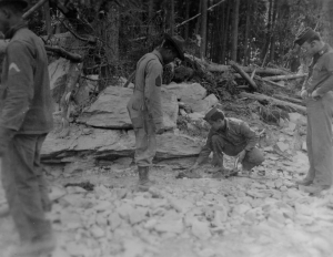 Capt. Trabeck and a black soldier setting dynamite under a boulder blocking the path of the Alaska Highway. 1942