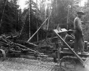 Black soldiers operating a dozer pulling an Adams grader over the Alaska Highway. 1942