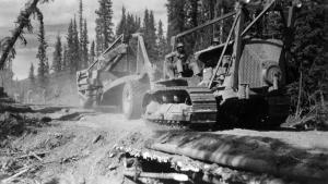 A black dozer operator driving a dozer hauling a carryall over a culvert. 1942