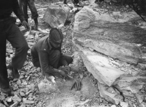 Capt. Traback and a black engineer setting explosives under a boulder in the path of the Alaska Highway. 1942