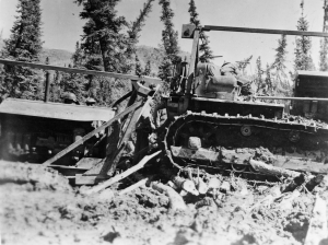 Along the Alaska Highway, one dozer is stuck in mud as a second dozer attempts to pull it free. 1942